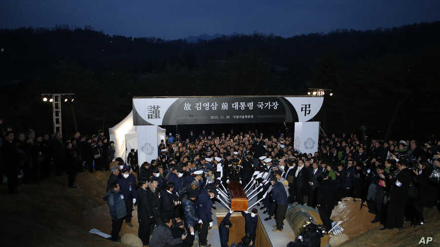 The coffin of the late former South Korean President Kim Young-sam is lowered by the honor guard during his burial ceremony at the national cemetery in Seoul, South Korea, Thursday, Nov. 26, 2015.