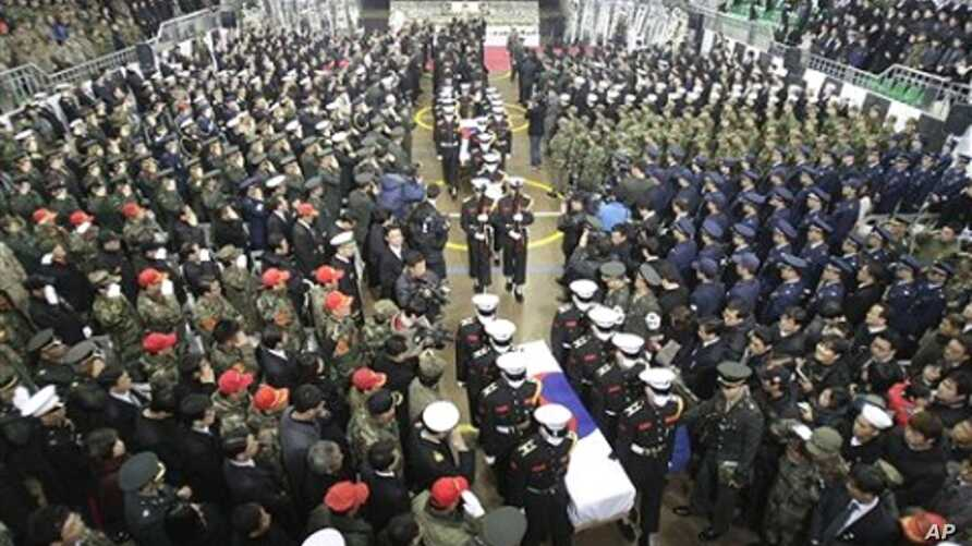 South Korean marines carry two flag-draped caskets containing the remains of marines killed in Tuesday's North Korean bombardment during a funeral service at a military hospital in Seongnam, South Korea, 27 Nov 2010