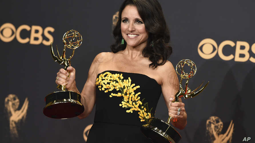 """FILE - Julia Louis-Dreyfus poses in the press room with her awards for outstanding lead actress in a comedy series and outstanding comedy series for """"Veep"""" at the 69th Primetime Emmy Awards at the Microsoft Theater in Los Angeles, Sept. 17, 2017."""