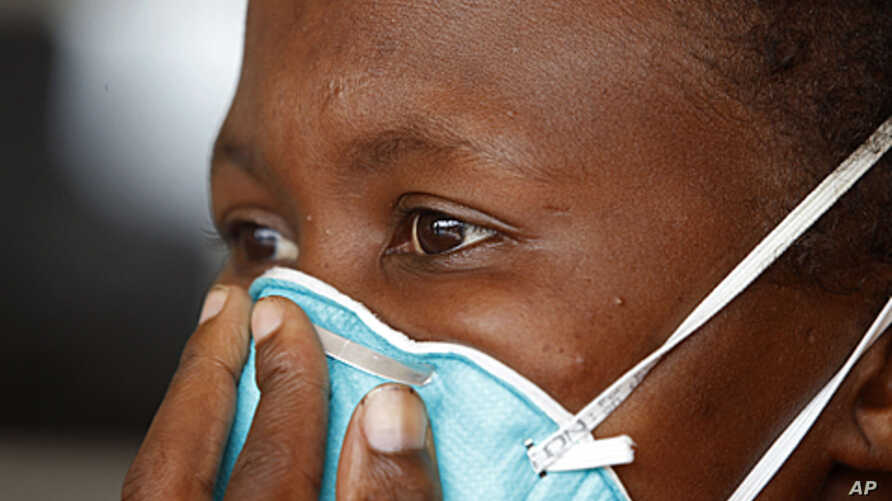 A woman suffering from tuberculosis covers her face at a clinic in the township of Khayelitsha, on the outskirts of Cape Town, South Africa, March 24, 2011