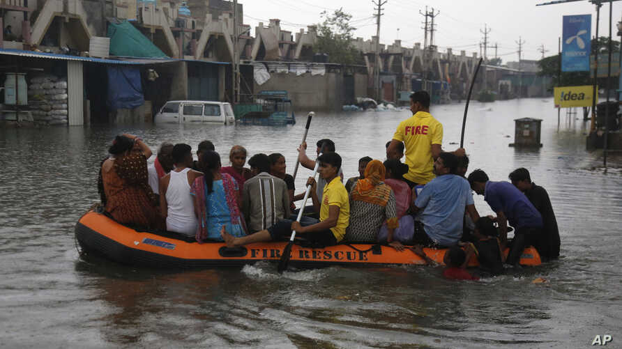 Indian fire officials rescue residents of an area which was flooded following incessant rains, in Ahmadabad, India, July 28, 2017.