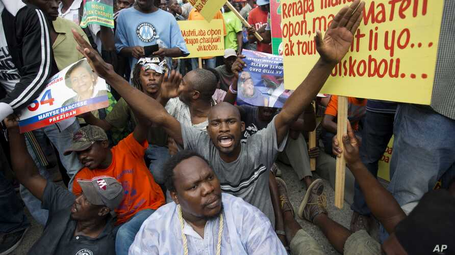 FILE - Demonstrators chant anti-electoral council slogans during a rally protesting against what they claim are fraudulent elections results in Port-au-Prince, Haiti, Dec. 16, 2015.