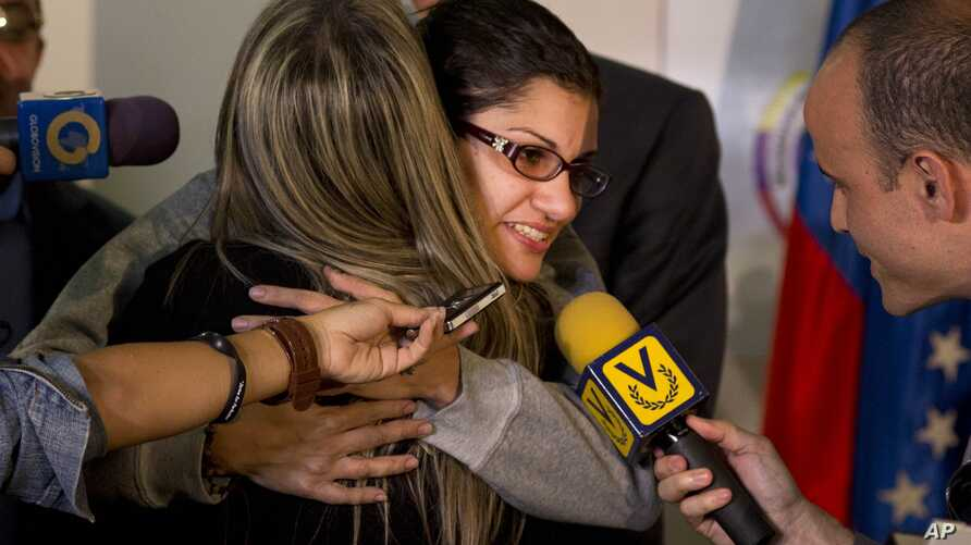 Globovision journalist Nairobi Pinto hugs a colleague as she answers a reporter's question after a press conference following her release from a kidnapping in Caracas, Venezuela, April 14, 2014.