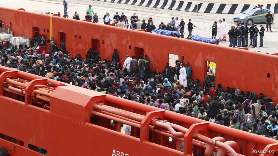 Migrants are seen aboard a navy ship before being disembarked in the Sicilian harbor of Augusta, June 1, 2014.