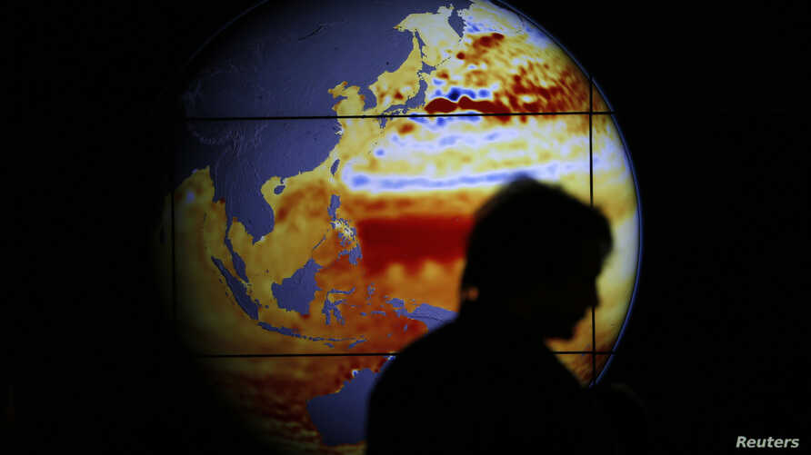 A woman walks past a map showing the elevation of the sea in the last 22 years during the World Climate Change Conference 2015 (COP21) at Le Bourget, near Paris, France, Dec. 11, 2015.