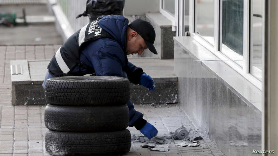 A police expert examines the remnants of a suspicious object after it was defused by sappers on a street in Kyiv, Ukraine, April 2, 2015.