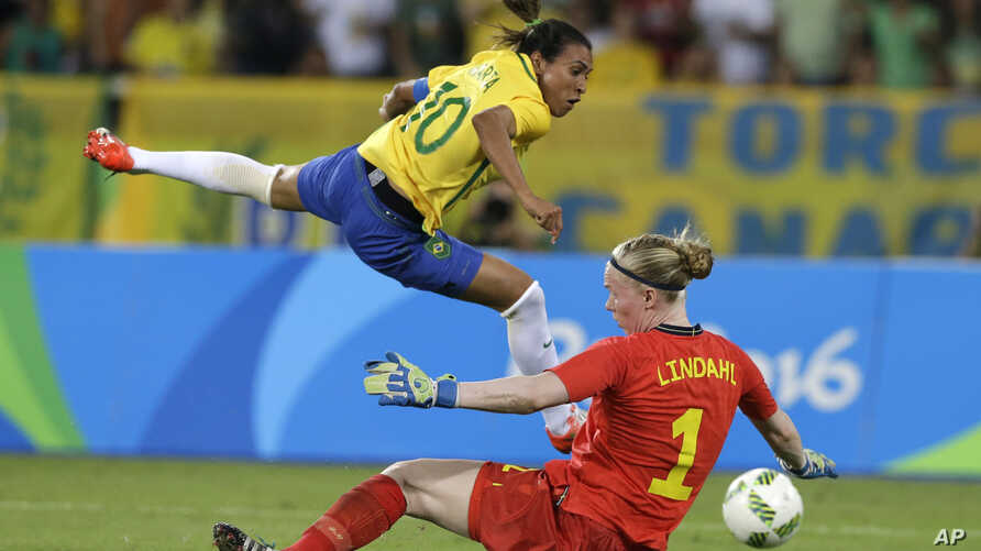 Brazil's Marta (L) leaps over Sweden goalkeeper Hedvig Lindahl as she attempts a shot on goal during a group E match of the women's Olympic football tournament between Sweden and Brazil at the Rio Olympic Stadium in Rio De Janeiro, Brazil, Aug. 6, 20