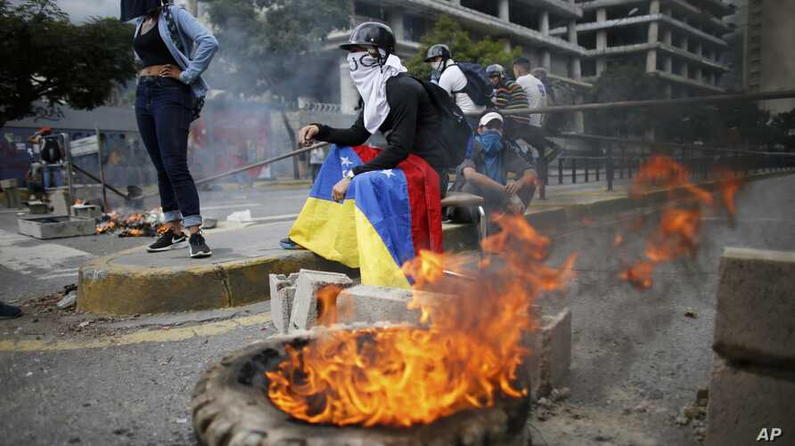 Masked anti-government demonstrators protest against the installation of a constitutional assembly in Caracas, Venezuela, Aug. 4, 2017. Defying criticism from Washington to the Vatican, Venezuela's ruling party Friday installed a new super assembly t...