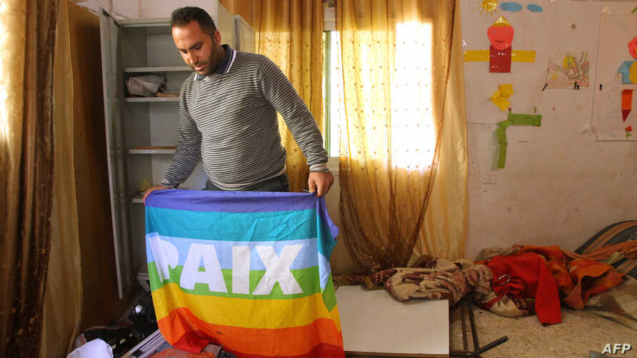 FILE - Issa Amro inspects an office of the Palestinian activist group Youth Against Settlements that was raided by Israeli troops in the occupied West Bank city of Hebron, Nov. 8, 2015.