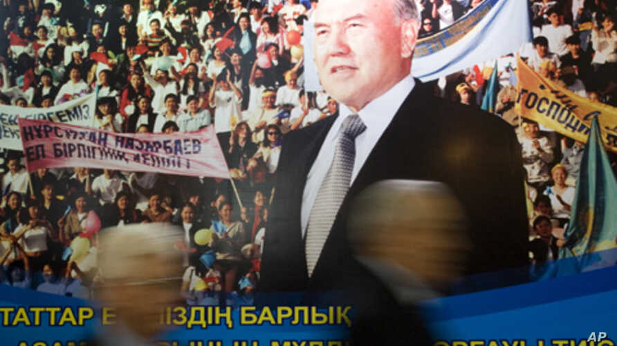 Parliamentary members walk past a poster of Kazakh President Nursultan Nazarbayev' after his annual state of the nation address, Astana, 2008 (FILE).
