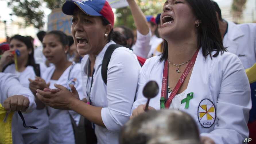 Nurses shout slogans during a protest against the government of President Nicolas Maduro, in Caracas, Venezuela, Aug. 16, 2018. The nurses were confronted by a phalanx of police officers that prevented them from marching toward Miraflores Presidentia