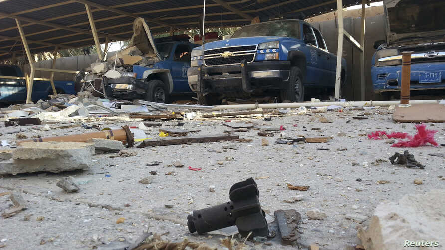 Police vehicles are parked next to debris in the Anbar province town of Hit, Iraq, Oct. 6, 2014.