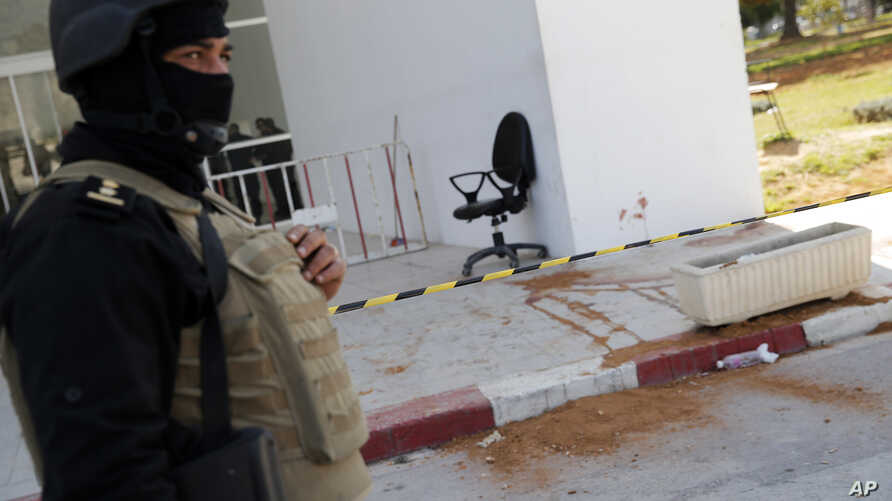 A policeman guard the entrance of the Bardo museum in Tunis, Tunisia, Thursday, March 19, 2015, as a a blood stain is seen at right,  a day after gunmen opened fire killing over 20 people, mainly tourists. One of the two gunmen who killed tourists an