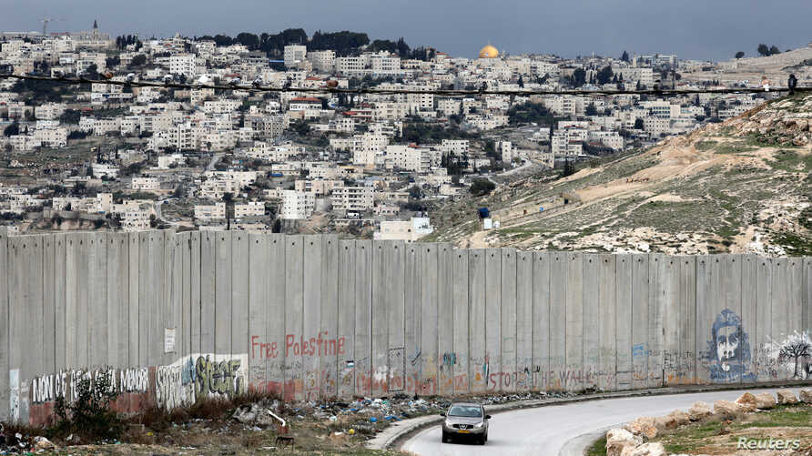 FILE - A car drives along a road near the Israeli barrier in the Palestinian town of Abu Dis in the West Bank, as Jerusalem is seen in the background, Feb. 15, 2017.