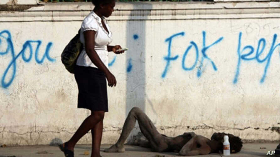 A woman walks past an unconscious man on a street just outside the quake-destroyed Presidential Palace in Port-au-Prince, Haiti, 16 Nov. 2010. The country's cholera death toll has passed 1,000 as the epidemic showed no sign of abating.