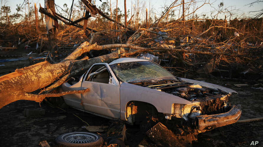 FILE - A car sits crushed by a fallen tree from a tornado as the sun rises in Beauregard, Ala., March 6, 2019. The National Weather Service The National Weather Service on March 9 issued tornado watches for parts of Tennessee, Mississippi, Louisiana