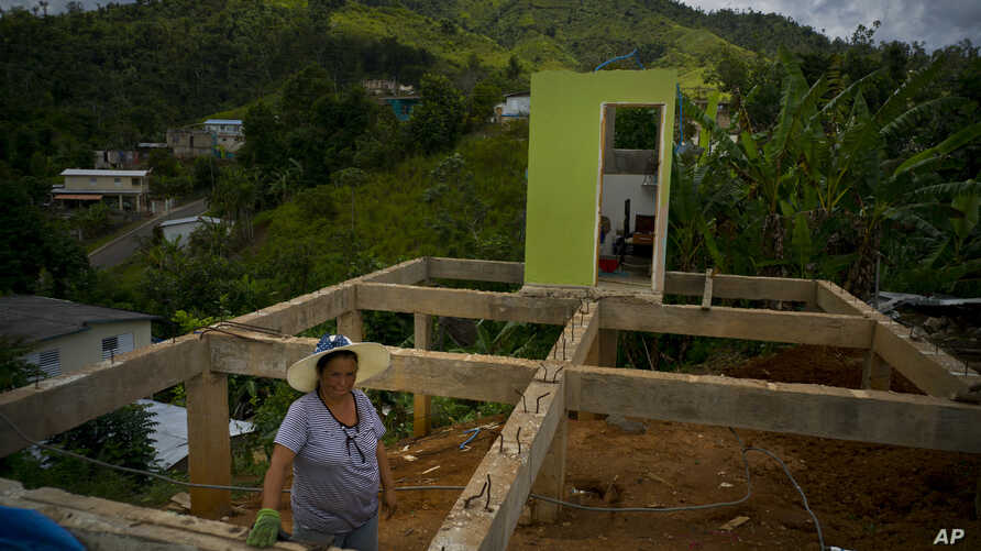 FILE - A woman poses for a portrait between the beams of her home being rebuilt after it was destroyed by Hurricane Maria one year ago in the San Lorenzo neighborhood of Morovis, Puerto Rico, Sept. 8, 2018.