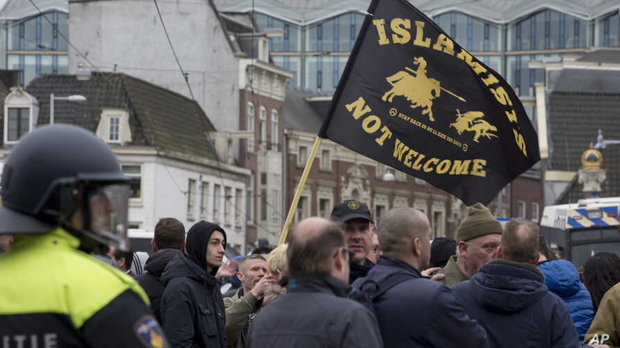 """Riots police separate pro and anti immigration demonstrators as a man waves a flag reading """"Islamists Not Welcome"""" during a Pegida demonstration in Amsterdam, Netherlands, Feb. 6, 2016."""