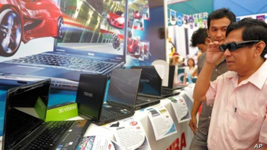 A customer (R) wears 3D glasses as he views a 3D movie on a Toshiba computer during an exhibition in Phnom Penh, Cambodia on September 11, 2010