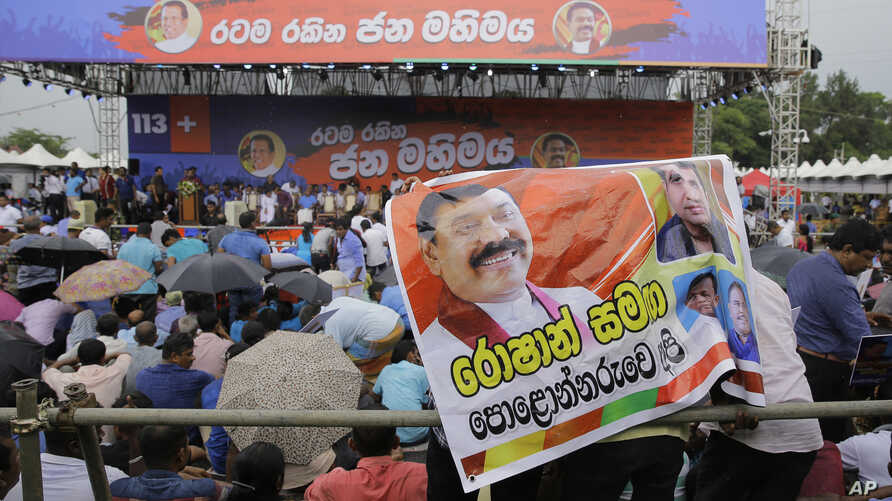 Supporter of Sri Lankan president Maithripala Sirisena and his newly appointed prime minister Mahinda Rajapaksa attend a rally held out side the parliamentary complex as police officer tries to control the crowd in Colombo, Sri Lanka, Nov. 5, 2018.