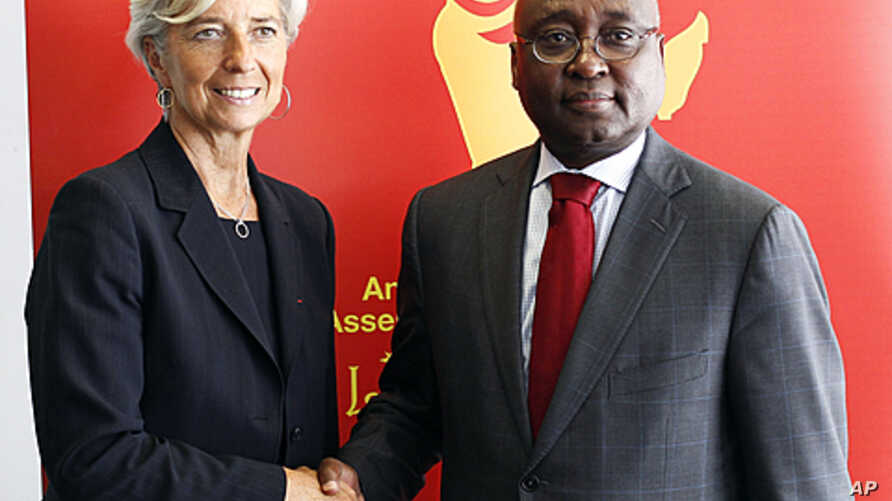 France's Financial Minister Christine Lagarde, left, shakes hands with Donald Kaberuka, President of the African Development Bank during the African Development Bank annual meeting in Lisbon, June 10, 2011.