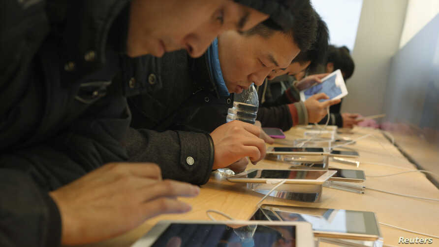 Customers test out Apple iPads in an Apple Store in downtown Shanghai, February 29, 2012.