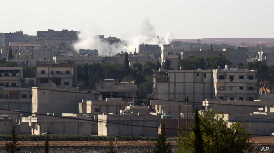 A mortar shelling lands in the residential area in Kobani in Syria, as seen from Mursitpinar near Suruc, Turkey, as fighting intensified between Syrian Kurds and the militants of Islamic State, Oct. 5, 2014.