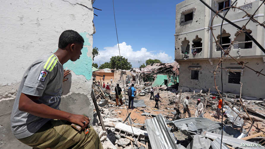 A Somali man watches the damage caused at the scene where a car exploded in the Madina district of Mogadishu, Somalia, May 17, 2017.