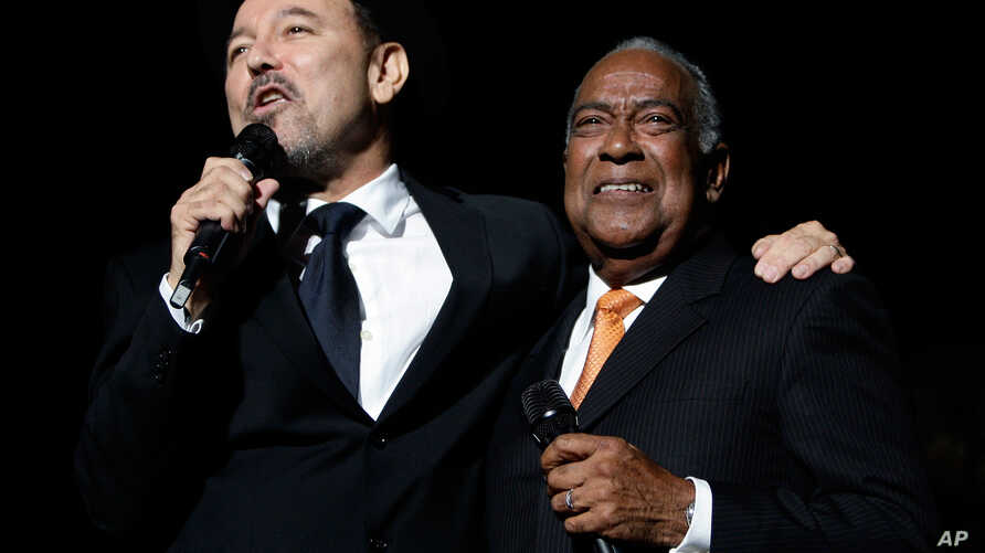 """FILE - Guest singer Cheo Feliciano, right, becomes emotional while listening to salsa music star Ruben Blades after signing together in the kick off of Blades' tour """"Todos Vuelven""""."""
