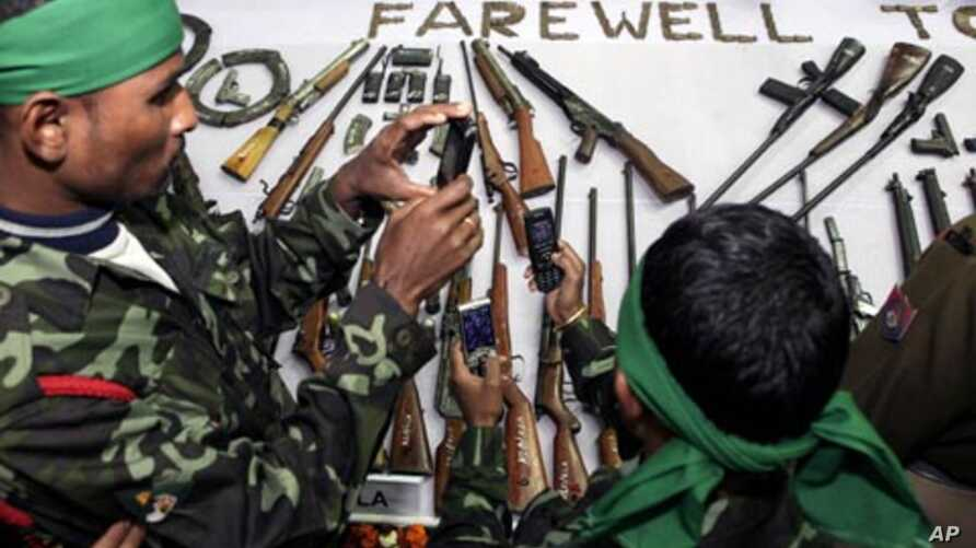Militants of the Assam separatist group take photographs of arms displayed during a surrender ceremony in Guahati, India, January 24, 2012.