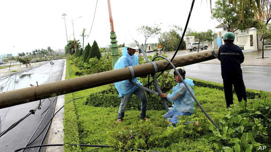 Workers repair a fallen electricity pole in the central province of Phu Yen, Vietnam, Saturday, Nov. 4, 2017. Typhoon Damrey slammed the south central coast of Vietnam on Saturday killing one person and leaving five others missing
