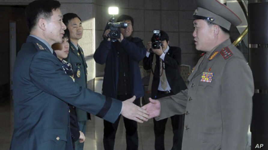 South Korean Colonel Moon Sang-gyun (L) shakes hands with his North Korean counterpart Ri Son-kwon before their talks at the south side of the truce village of Panmunjom in Paju, north of Seoul, February 9, 2011