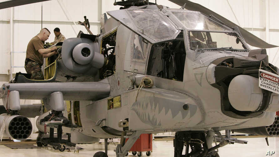FILE - A service member works on an Army National Guard Apache helicopter.