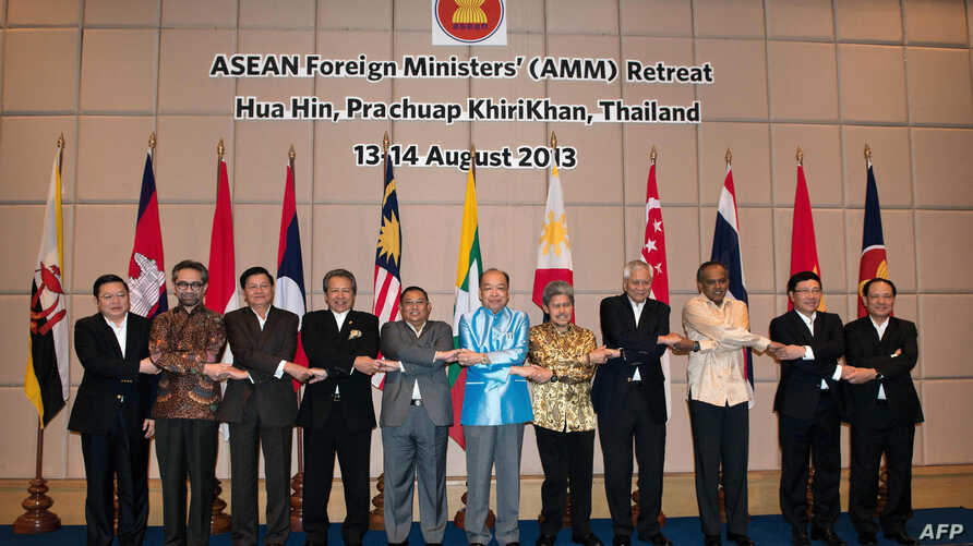 Association of Southeast Asian Nations foreign ministers and Secretary General Le Luong Minh join hands as they pose for a group photograph during the ASEAN foreign ministers meeting in Hua Hin, Thailand, August 14, 2013.