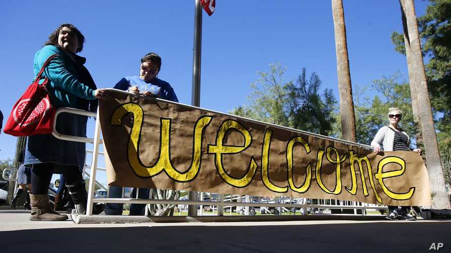 Supporters place a sign welcoming Syrian refugees is placed at the entrance to the office of the Arizona governor during a rally at the Arizona Capitol in Phoenix, Nov. 17, 2015.