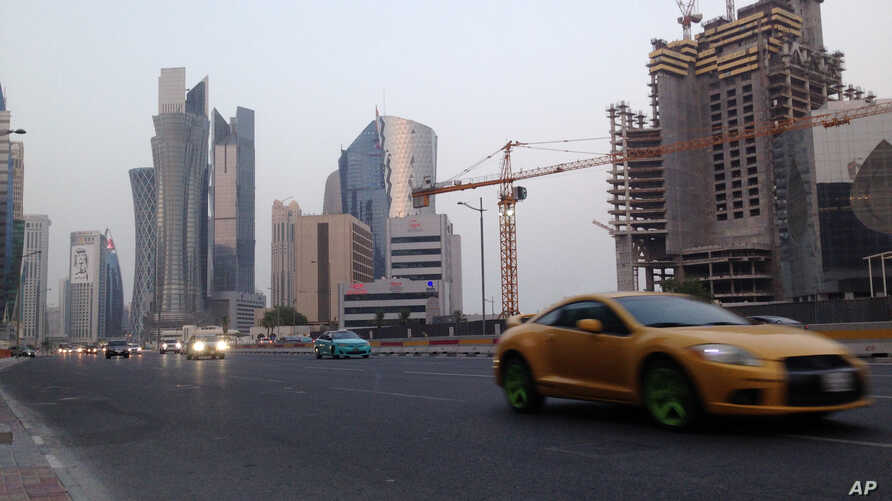 In this July 10, 2017 photo, a sports car drives through downtown Doha. As the Gulf crisis over Qatar festers, Secretary of State Rex Tillerson embarks on his first shuttle diplomacy mission, in a bid to end a deadlock that has damaged ties between k