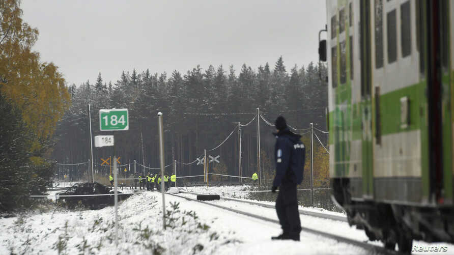 Rescue and military personnel and a policeman are seen at the railroad crossing after a crash between a train and a military truck in Raseborg, Finland, Oct. 26, 2017.