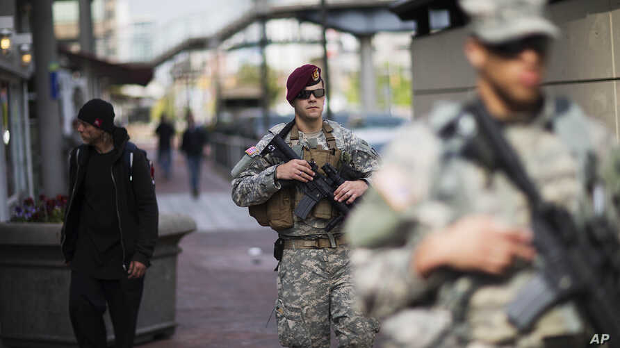 Members of the National Guard patrol along the Inner Harbor in the aftermath of rioting following Monday's funeral for Freddie Gray, who died in police custody, April 30, 2015, in Baltimore.