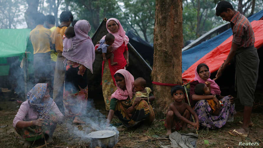 Rohingya refugees go about their day outside their temporary shelters along a road in Kutupalong, Bangladesh, Sept. 9, 2017.