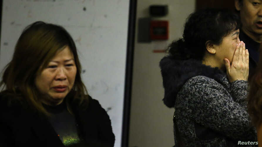 Relatives of passengers onboard the missing flight MH370 react as they wait for news at a hotel in Beijing, March 21, 2014.