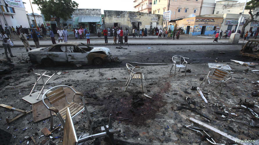 People gather in the aftermath of an explosion that happened Sunday night outside the Oromo restaurant in Mogadishu, Oct. 13, 2014.