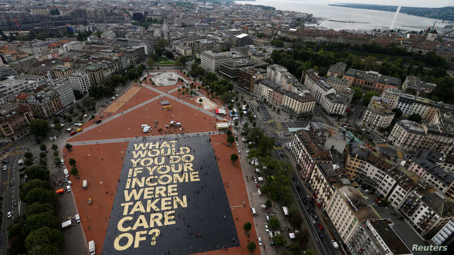 """FILE - An 8,000-square-meter poster is pictured on the Plainpalais square in Geneva, Switzerland May 14, 2016. Swiss citizens will vote on the proposal for an """"Unconditional Basic Income,"""" June 5, 2016."""