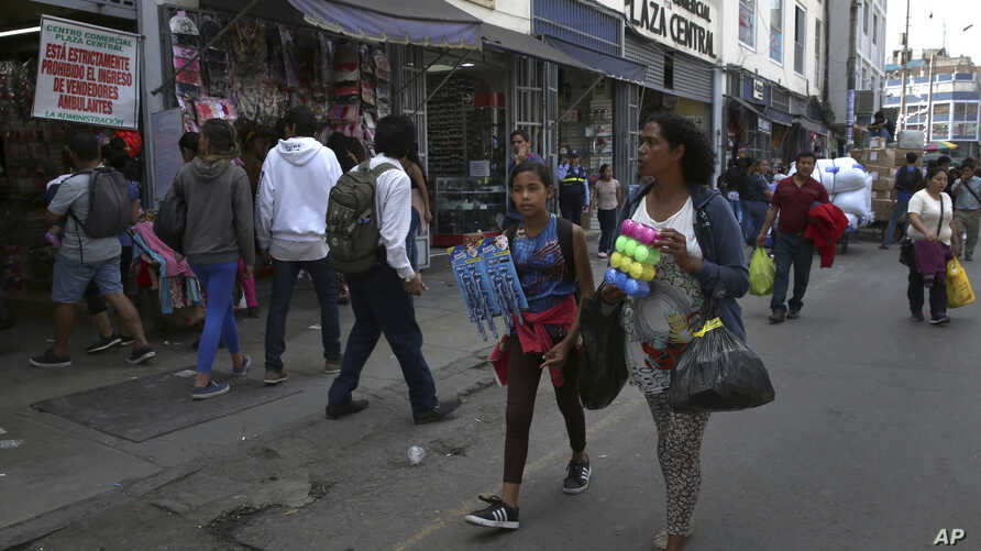 Venezuelan Sandra Cadiz and her 10-year-old daughter Angelis walk try to sell cotton swabs and razors near the Central Market in Lima, Peru, Oct. 9, 2018.