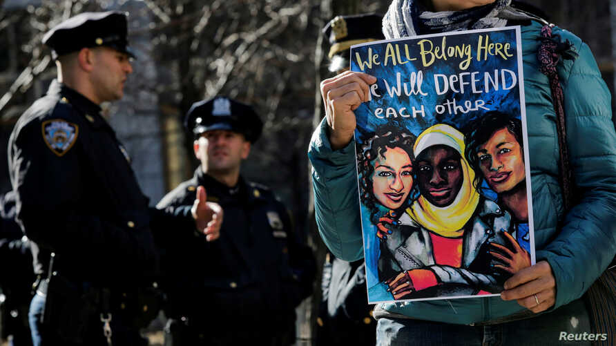 People take part in a rally in front of the Jacob K. Javits Federal Office Building denouncing the targeting of immigrant activists by Immigration Customs Enforcement while New York Police Department officers stand guard, New York, Jan. 27, 2018.