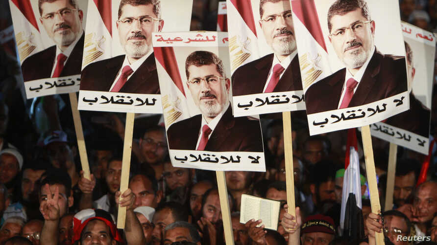 Supporters of deposed Egyptian President Mohamed Morsi hold his posters during a protest at the Rabaa al-Adawiya square where they are camping, in Cairo, Aug. 6, 2013.