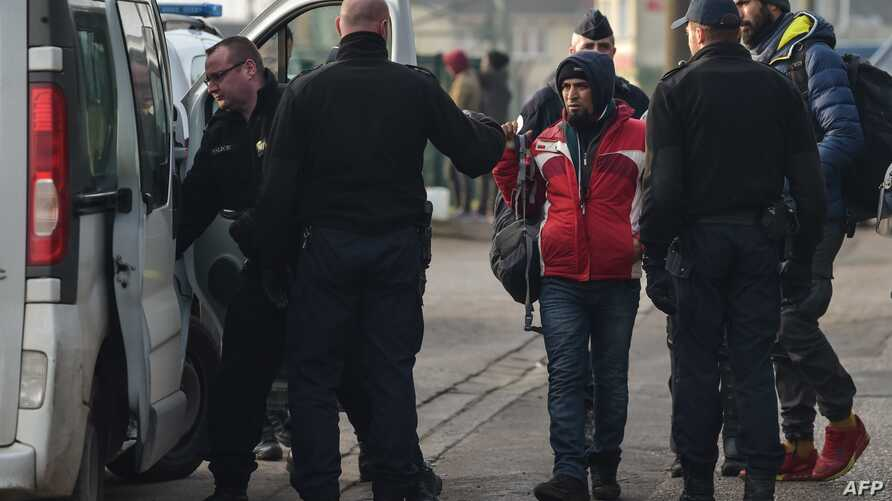 FILE - Police forces arrest migrants as they evacuate their camp in Calais, Feb. 21, 2019..