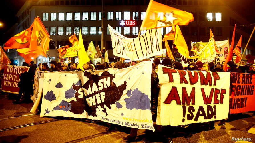 Protesters carry banners during a demonstration against U.S. President Donald Trump, ahead of Trump's visit to the World Economic Forum (WEF), in Zurich, Switzerland, Jan. 23, 2018.