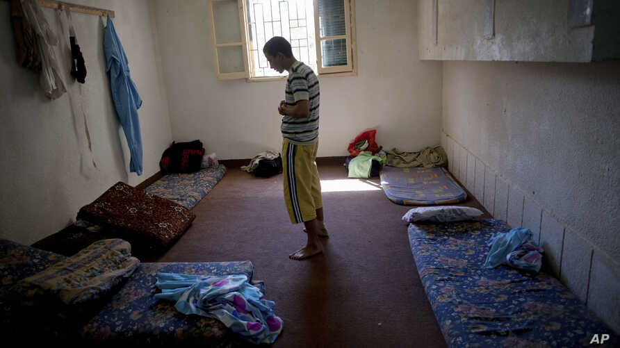 FILE - A man suspected of being a Gadhafi loyalist prays in a detention facility run by former rebel fighters in Misrata, Libya, Sept. 22, 2011.