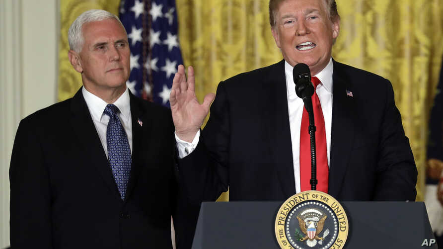 President Donald Trump speaks during a meeting of the National Space Council in the East Room of the White House, June 18, 2018, in Washington, as Vice President Mike Pence looks on.