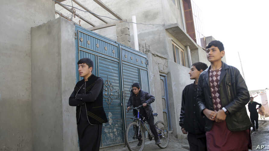 Residents walk pass the house in which Islamic State insurgents were hidden, in a street of Qala-e-Walid neighborhood in Kabul, Afghanistan, Feb. 2, 2018.